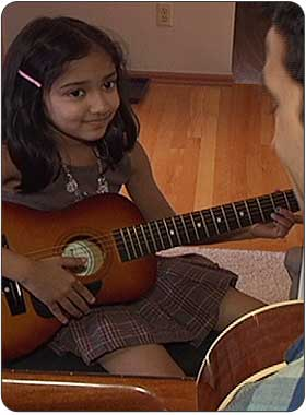 child enjoying advanced private guitar lesson