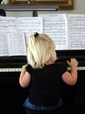child enjoying in home piano lesson